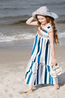 Girl on a sunny day at the beach in blue stripe maxi dress and light grey floppy hat with