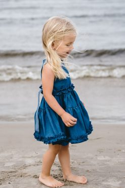 Blonde toddler girl on a beach in summer in a beautiful blue denim dress with ruffle detail, for kids, toddler, girl